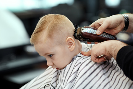 Cute blond baby boy with blue eyes in a barber shop having haircut by hairdresser. Hands of stylist with tools. Children fashion in salon. Indoors, dark background, copy space.
