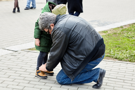 Senior man tying the laces on a child boots. Father or grandfather helps his little son or grandson. The both wearing casual. Outdoors, copy space.