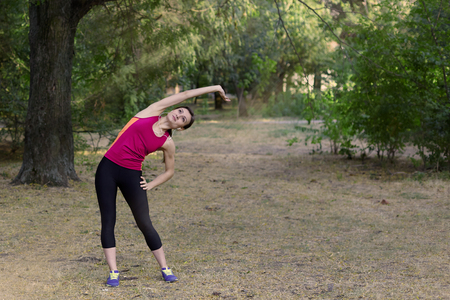 Gorgeous young slim woman makes gym in morning park. Side tilt, bright sportswear, white earphones, calmness and relax atmosphere, stretching training. Outdoors, copy space.