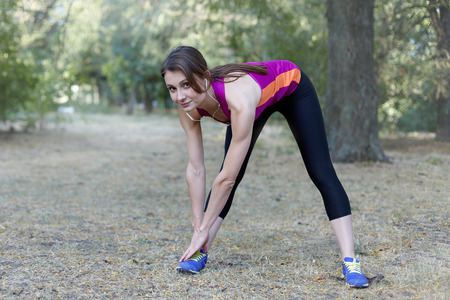 Gorgeous young slim woman makes gym in morning park. Tilt down, bright sportswear, white earphones, calmness and relax atmosphere, stretching training. Outdoors, copy space. Stock Photo