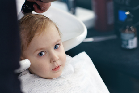 Serious and little scared cute blond baby boy with blue eyes in a barber shop having washing head by hairdresser. Children fashion in salon. Indoors, dark background, copy space. Stock Photo