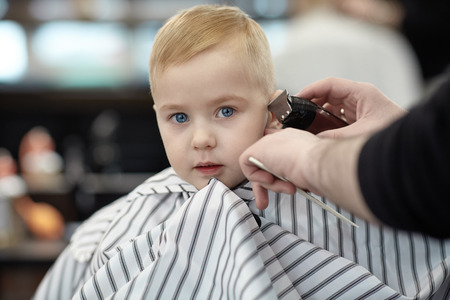 Serious cute blond baby boy with blue eyes in a barber shop having haircut by hairdresser. Hands of stylist with tools (trimmer, brush). Children fashion in salon. Indoors, dark background, copy space. Stock Photo