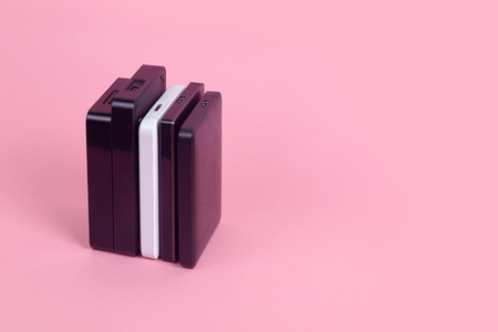 Some external hard drives for storing data, backups and security information. Pink background, isolated, copy space.