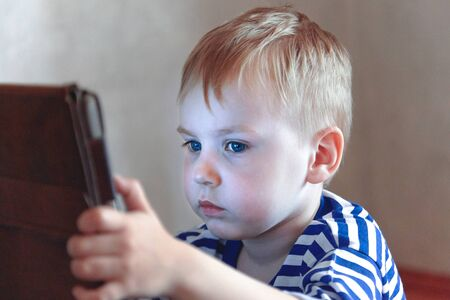 Little caucasian baby boy uses a tablet, seeing to the screen. Children time spending, computerization of youngsters. Red hair, casual wear, indoors, close up, copy space. Stock Photo