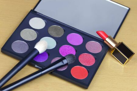 Big eye shadow palette of many colors in lilac, violet and red tones, with two cosmetic brushes and opened red lipstick in luxury tube, settled on light wooden background. Close up, copy space.
