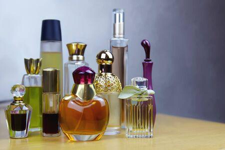 Einige bunte Parfümflaschen auf Holztisch. Alte Vintage-Parfums. Selektiver Fokus, grauer Hintergrund, drinnen, Kopierraum.