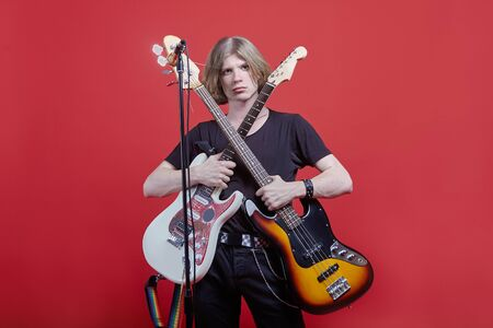 Young handsome caucasian man stands with two guitar, acoustic and electric ones in front of the stack with microphone. Musician posing in studio, black casual wear, rainbow color belt, red background, copy space.