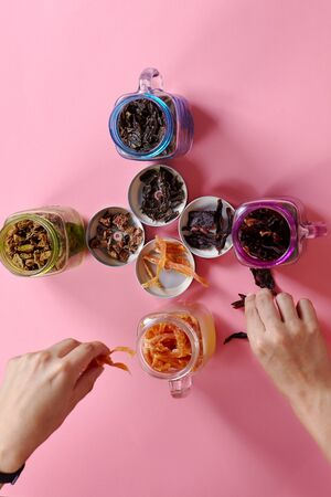 Woman hands setting out the pieces of dry products (meat or fruit) in glass jars on pink background. Food photographer or designer working process. Indoors, top view, selective focus, copy space.