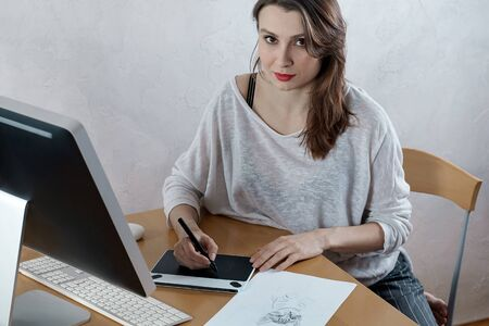 Young attractive caucasian woman, artist or graphic designer, draws kitten on graphic tablet at the home office. Woman freelance. Indoors, copy space.