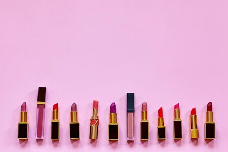 Many colorful opened lipsticks, setting in a raw on bright pink background.. Chic design, red, lilac and nude tones. Copy space for any text, close up. Фото со стока