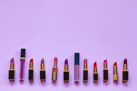 Many colorful opened lipsticks, setting in a raw on bright lilac background.. Chic design, red, lilac and nude tones. Copy space for any text, close up. Фото со стока