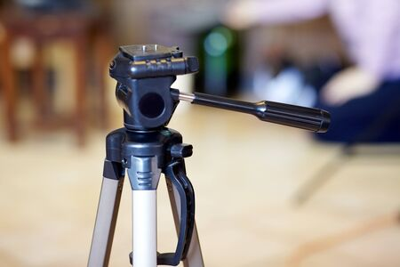 Empty tripod for camera on blurred background, for photo and video shooting. Indoors, copy space, selective focus.