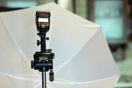 Black camera tripod with studio lightning equipment on blurred background, white umbrella for professional photo and video shooting. Indoors, copy space, selective focus.