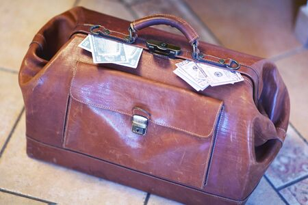 Old vintage red leather case full of money coming out of the sides. Scratched bag on ceramic floor. Business, bribe or prize concept. Indoors, copy space.