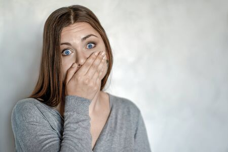 Young attractive caucasian woman covers the mouth with hand, grimace of astonishment or shock. Blue eyes, strong emotions, wow expression. Selective focus, copy space.