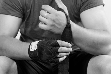 Black and white shor of caucasian man torso in sportswear, bandaging his hands with boxing bandages, sitting. Moment before match or training. Indoors, copy space, close up. Stok Fotoğraf