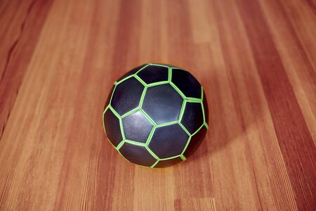 The black and green ball for football or volleyball playing, in the center of composition. Indoors, selective focus, blur background. Sport or fintess concept, copy space.  Imagens