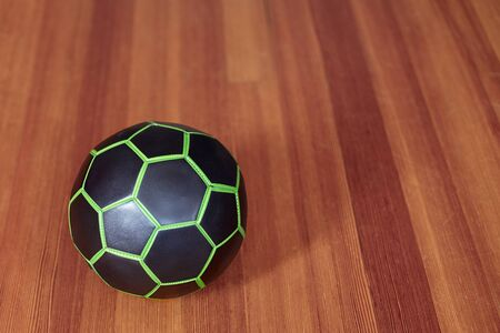 The black and green ball for football playing, in the left of composition. Indoors, selective focus, blur wooden background. Sport or fintess concept, copy space.