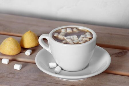 The cup of hot cocoa with marshmallows and yellow sweeties on wooden table. Cosy atmosphere of autumn or winter morning. Copy space. Stock Photo