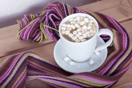 The big light lilac cup of hot cocoa with marshmallows on the bright striped scarf, on wooden table. Melancholy mood, atmosphere of cold autumn or winter morning. Copy space.