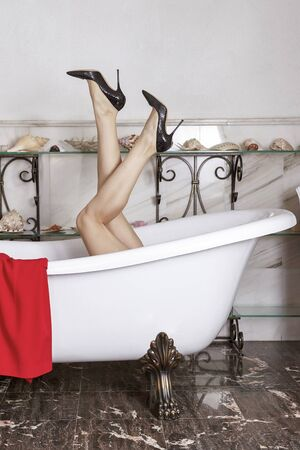 Woman legs in black high heels, sticking out from emtpy antique bathtub on lion paws. Luxury vintage design of bathroom with marble walls and floor, sea shells on the shelves. Indoors, copy space.