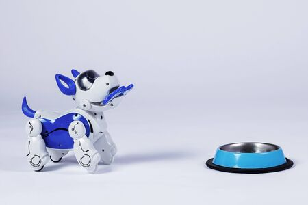 Electronic interactive toy dog puppy with a bone in mouth stands in front of empty pet bowl. High technology concept of future domestic animals in electronic home. Indoors, copy space. Stok Fotoğraf