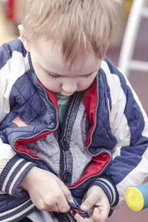 Cute blond caucasian baby boy tries to fasten the zipper the jacket. Independent kid on outdoor walking. Copy space. Stock Photo