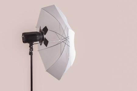 The light equipment of photo studio, on pinkish grey background. Isolated, copy space for any text.