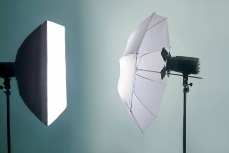 The light equipment of photo studio, on blue background. Isolated, copy space for any text.