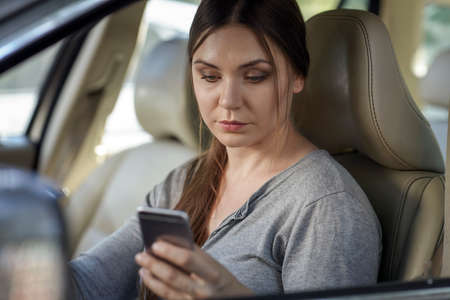 Young attractive caucasian woman behind the wheel driving a car with mobile phone in hand in traffic jam. Looking to the screen, danger situation, bad habit. Blue eyes, dard hair, round shape face. Copy space.