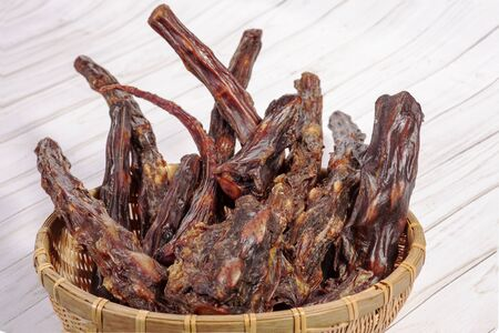 Straw bowl full of dried oxtails. Could be used in exotic cuisine or as natural chew treats for big dogs. Dehydrated foods. Indoors, white background, copy space. Foto de archivo