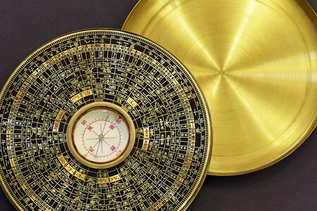Old vintage chinese compass used in feng shui, golden item with hieroglyphs and cover, on dark background. Studio, copy space.