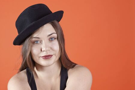 Young attractive caucasian brunette woman with bright blue eyes and dark lipstick, wearing black bowler hat, smiles looking right to the camera. Isolated on coral background, studio, copy space.