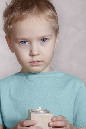 Beautiful and serious caucasian little boy looks right to the camera, holding the burning candle in both hands. Stunning blue eyes, sad face expression.