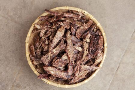 Top view on dehydrated homemade pet beef lungs chips in straw pot on stone background. Dog and cat chewy jerky and treats. Outdoors, close up, soft selective focus, copy space.