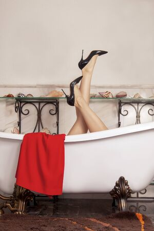 Woman legs in black high heels, sticking out from empty antique bathtub on lion paws. Luxury vintage design of bathroom with marble walls and floor, sea shells on the shelves. Indoors, copy space. Imagens