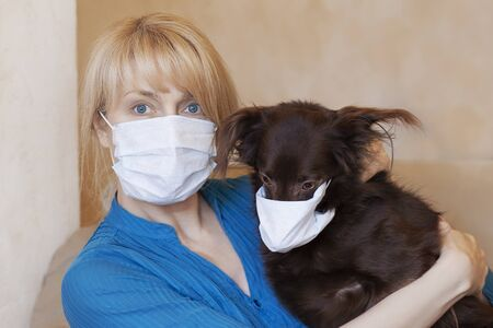 Middle aged woman with blond hair holds little brown dog in hands, the both are in sanitizing masks. Virus and protective measures at home concept, safety for animals and their owners. Indoors, copy space.