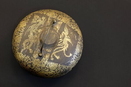 Old vintage chinese dark metal pot with golden items drawn on surface, dragons and flowers theme. Asian ancient item. Black background, studio, copy space. Imagens