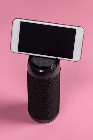 Black cylinder of portable wireless bluetooth speaker for music listening with mobile phone inserting in the housing in stand with special grooves. Bright pink background, studio, copy space for any text or advertisement.