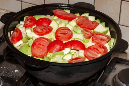 Big cast iron pot, full of vegetables, stewing on stove. Bright red tomatoes and zucchini, vegeterian food, healthy meal concept. ?oarse salt scattered everywhere.