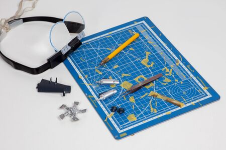 Special equipment for aeromodelling, forceps, cutter, glasses, details of assembled plane, propeller, blades, parts of wings and dirty fragmented substrate with the spots of previous work. Man hobby.