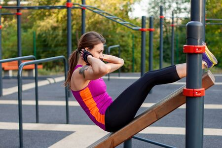 Young attractive Caucasian woman wearing bright sport clothes, tight pants and white earphones has an abdominal training at outdoor fitness ground. Summer morning, healthy lifestyle, copy space.