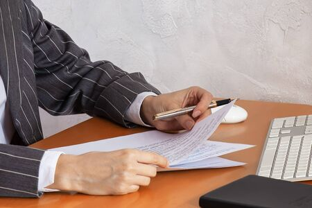 Close up hands of business woman wearing gray striped suit, holding expensive pen and paper documents. White keyboard and computer mouse, black notebook lying on wooden table, light background wall.