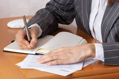 Close up hands of business woman wearing gray striped suit, and writing with expensive pen in notebook lying on wooden table. Paper documents, white computer mouse, light background wall. Indoors.
