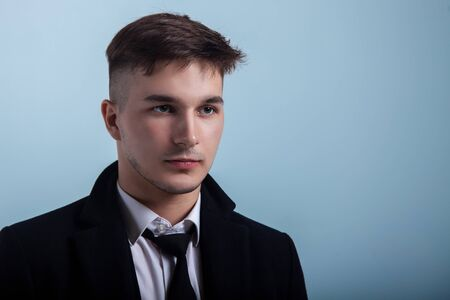 Portrait of young handsome man with attentive look on greyish blue background. Trendy hairstyle, expressive face, little beard, classic official black suit. Studio, copy space.