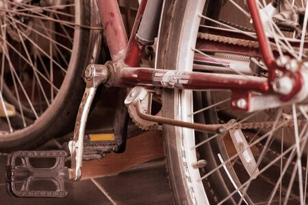 Two old dusty bicycles standing in closet under the stairs. Close up wheel, spokes, transmission chain and pedals. Copy space.  Imagens