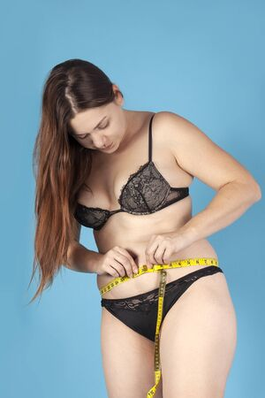 Young overweighted woman in black underwear measuring her waist with yellow tape. Healthy lifestyle, odd weight or body positive concept. Standing on bright blue background, studio, copy space.