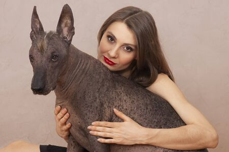 Young attractive woman embracing Mexican Hairless dog, or Xoloitzcuintle breed. Female with dark hair, eyes and red lipstick, smiling, beautiful pet with attentive look and irokez on head.