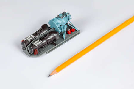Plastic model of helicopter engine and main gear collected and painted by hand. Avia modeling hobby, scale of miniature with the pencil. White background, copy space. Imagens