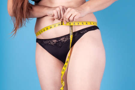 Little over-weighted woman in black underwear measuring her waist with yellow tape. Healthy lifestyle, odd weight or body positive concept. Standing on bright blue background, studio, copy space. Imagens